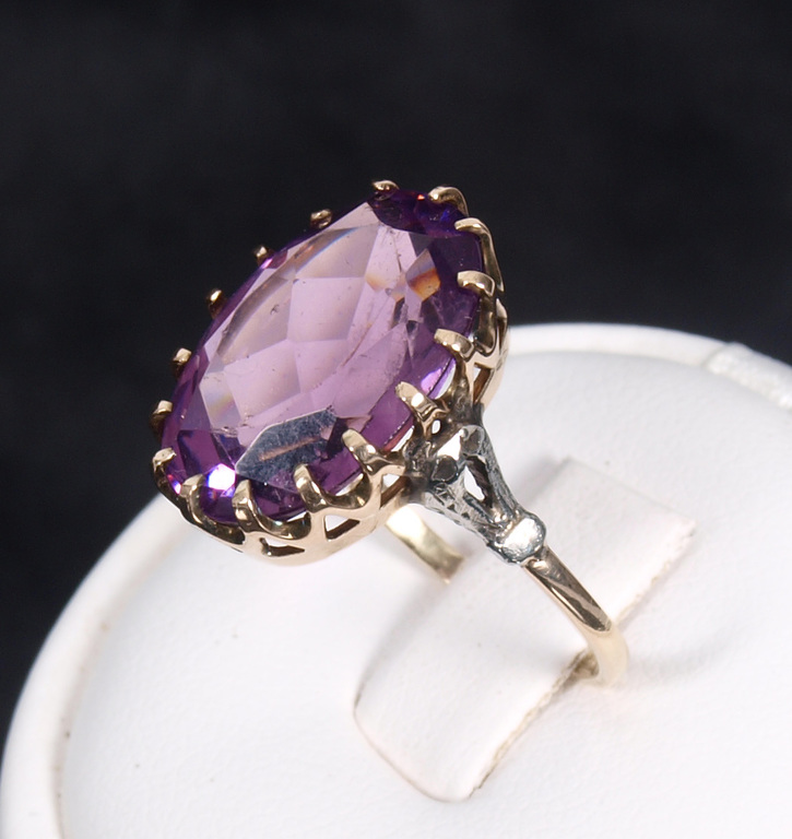 Golden ring with a purple stone