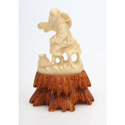 Bone figurine on the wood base